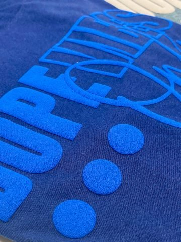 close up side view of a walakut puff vinyl in blue on a blue shirt