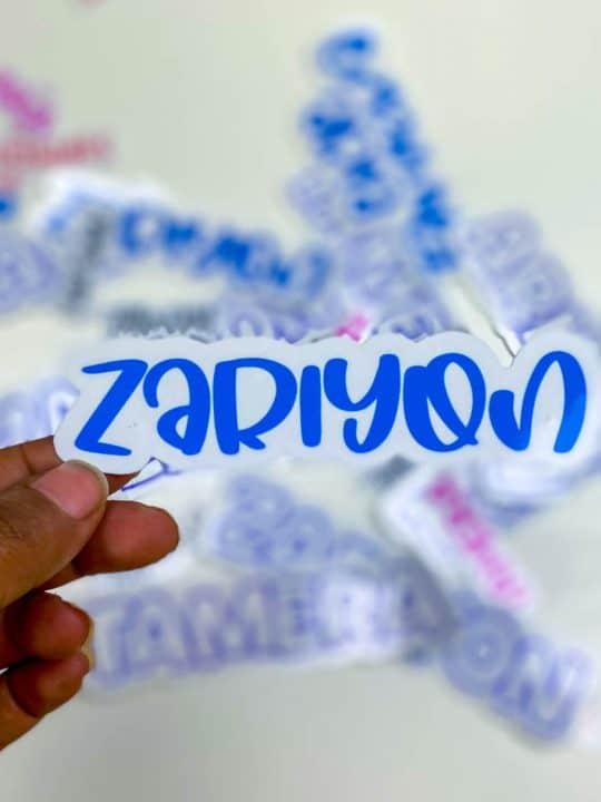 hand holding a blue sticker that says ZaRiyon.