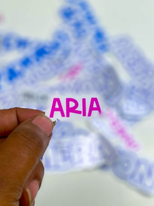 hand holding a pink sticker that says Aria